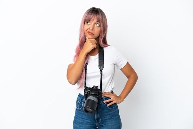 Giovane fotografo di razza mista donna con i capelli rosa isolato su sfondo bianco avendo dubbi