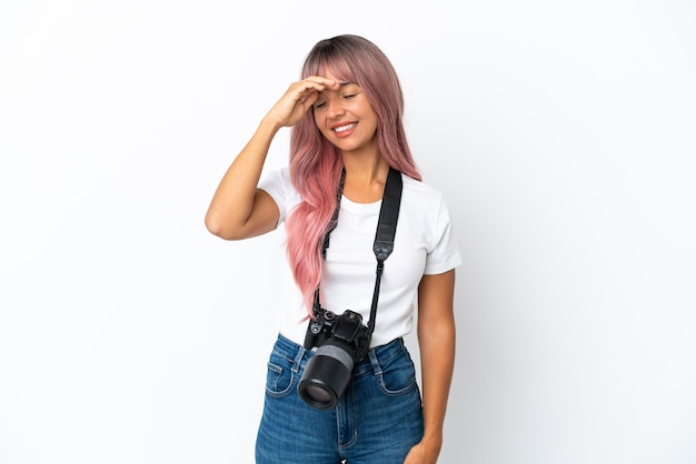 Giovane fotografo di razza mista donna con i capelli rosa isolato su sfondo bianco sorridente molto
