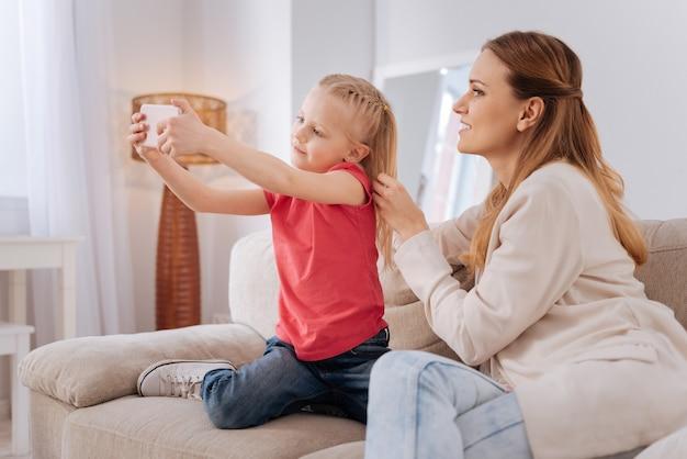 Giovane fotografo. piacevole ragazza bionda allegra che sorride e che prende un selfie mentre è insieme a sua madre