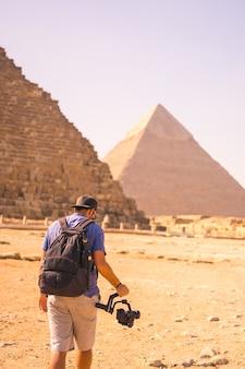 Un giovane fotografo alla piramide di cheope, la piramide più grande. le piramidi di giza il più antico monumento funerario del mondo. nella città del cairo, in egitto