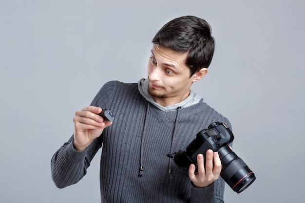 Il giovane fotografo in camicia imposta la fotocamera. ragazzo impara a fotografare su sfondo grigio