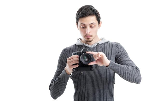 Il giovane fotografo in camicia installa la macchina fotografica isolata su fondo bianco. ragazzo impara a fotografare