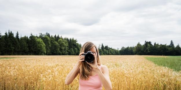 Giovane fotografo in piedi da un bellissimo campo di grano dorato che scatta foto direttamente alla fotocamera.