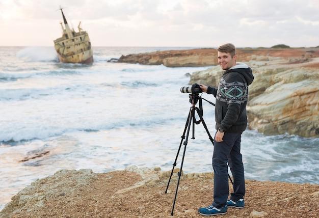 Giovane fotografo con lo zaino che fa foto di mare e scogli con la fotocamera.