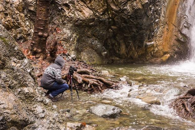 Giovane fotografo con lo zaino che fa le foto della cascata e delle rocce con la macchina fotografica.