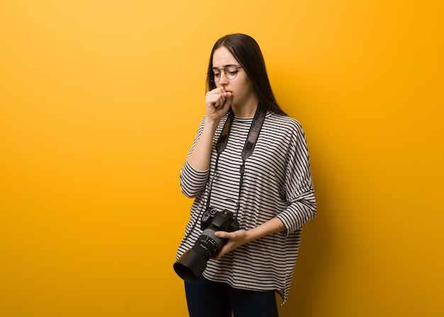Giovane fotografa donna che tossisce, si ammala a causa di un virus o di un'infezione