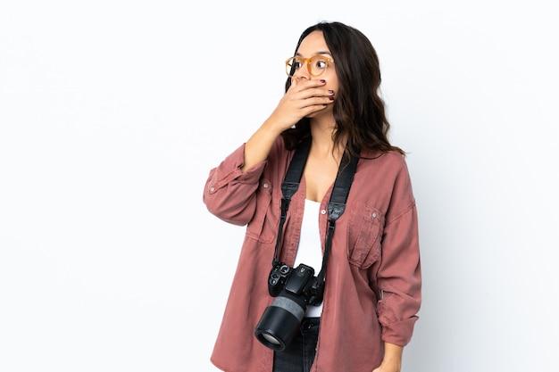 Giovane donna del fotografo sopra bianco isolato che fa gesto di sorpresa mentre guardando al lato