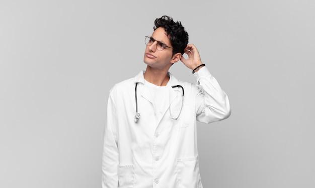 Giovane medico che si sente perplesso e confuso, grattandosi la testa e guardando di lato