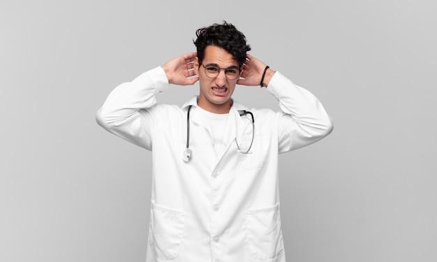 Giovane medico che si sente stressato, preoccupato, ansioso o spaventato, con le mani sulla testa, in preda al panico per errore