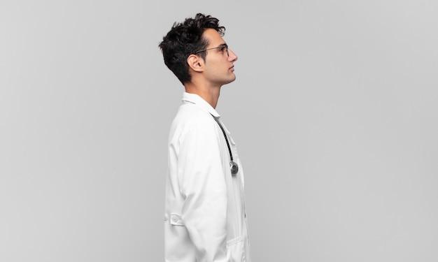 Giovane medico sulla vista di profilo che cerca di copiare lo spazio davanti, pensare, immaginare o fantasticare