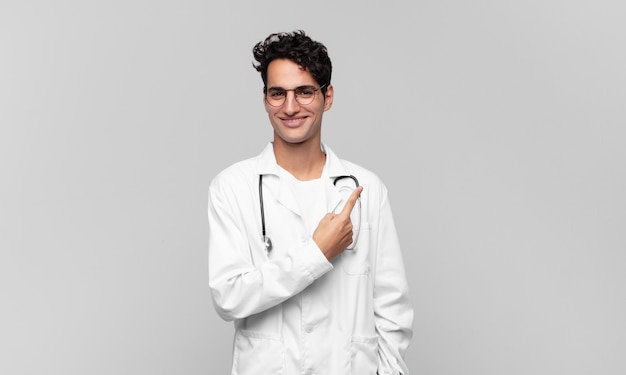 Giovane medico che sorride allegramente, si sente felice e indica di lato e verso l'alto