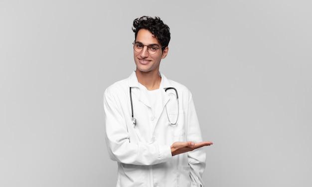Giovane medico che sorride allegramente, sentendosi felice e mostrando un concetto nello spazio della copia con il palmo della mano