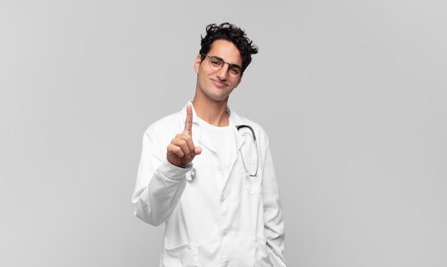 Giovane medico che sorride con orgoglio e sicurezza facendo posare trionfante il numero uno, sentendosi come un leader