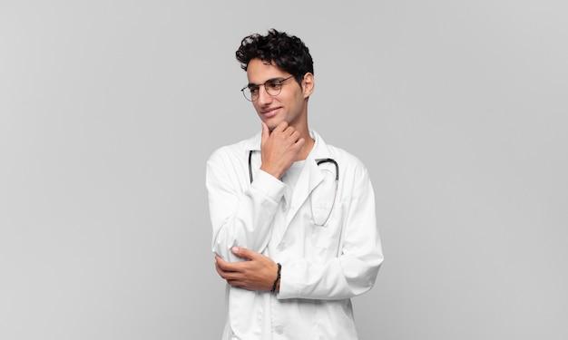Giovane medico che sorride con un'espressione felice e sicura con la mano sul mento, chiedendosi e guardando di lato