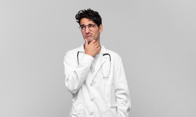 Giovane medico che pensa, si sente dubbioso e confuso, con diverse opzioni, chiedendosi quale decisione prendere