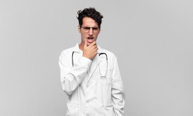 Giovane medico con la bocca e gli occhi spalancati e la mano sul mento, che si sente spiacevolmente scioccato, dice cosa o wow