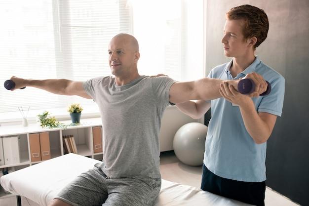 Giovane fisioterapista in polo blu che tiene il braccio teso del paziente con manubri durante l'esercizio di riabilitazione nelle cliniche