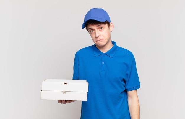 La giovane pizza consegna un ragazzo che sembra perplesso e confuso, mordendosi il labbro con un gesto nervoso, non conoscendo la risposta al problema
