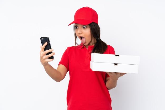 Giovane ragazza delle consegne della pizza su sfondo bianco isolato che tiene il caffè da portare via e un cellulare