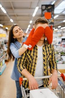 Giovane coppia giocosa, shopping nel negozio di casalinghi. uomo e donna che acquistano beni per la casa nel mercato, famiglia nel negozio di articoli da cucina