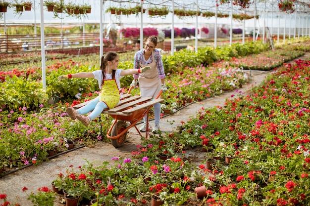 Giovane fiorista giocoso godendo il lavoro mentre uno di loro in sella al carrello in serra