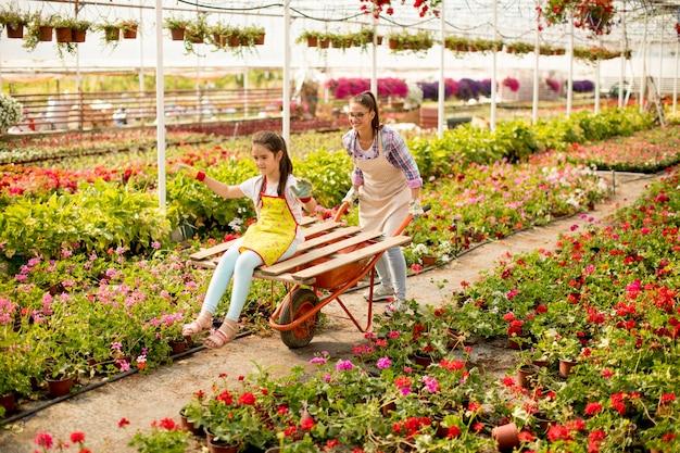 Giovane fiorista giocoso godendo il lavoro mentre uno di loro a cavallo nel carrello in serra