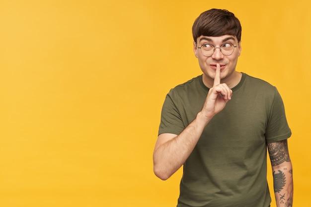 Giovane maschio giocoso con acconciatura elegante e occhiali rotondi, indossa una maglietta verde, mostra il gesto del silenzio e guarda da parte lo spazio della copia
