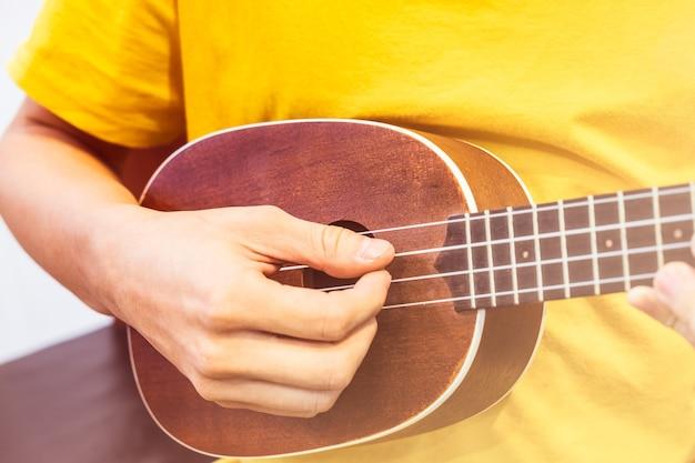 Giovane che suona ukulele in legno lucido