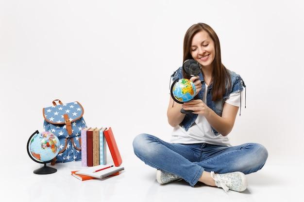 Giovane studentessa attraente e piacevole che guarda il globo usando la lente d'ingrandimento seduto vicino allo zaino, libri di scuola isolati sul muro bianco