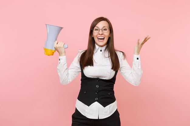 Giovane bella donna d'affari piacevole in tuta, occhiali che tengono le mani allargate del megafono isolate su sfondo rosa pastello. signora capo. concetto di ricchezza di carriera di successo. copia spazio per la pubblicità.