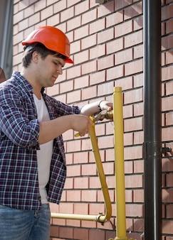 Giovane idraulico in elmetto protettivo che ripara tubi