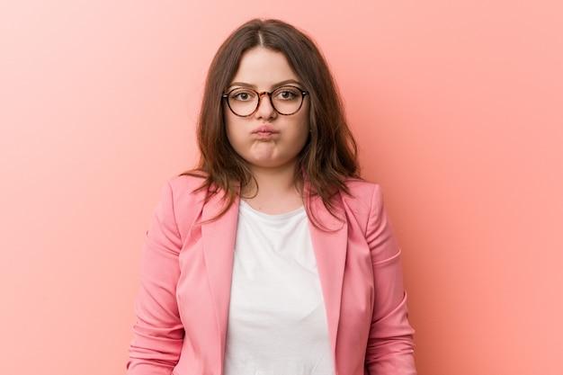 Giovane donna d'affari plus size caucasica soffia le guance, ha un'espressione stanca. concetto di espressione facciale.