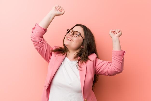 Giovane donna caucasica di affari di dimensioni più grandi che celebra un giorno speciale, salta e alza le braccia con energia.