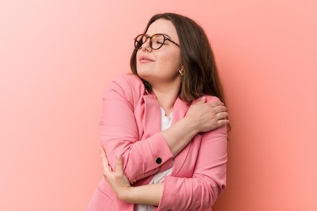 La giovane donna caucasica di affari di dimensione più si abbraccia, sorridendo spensierata e felice.