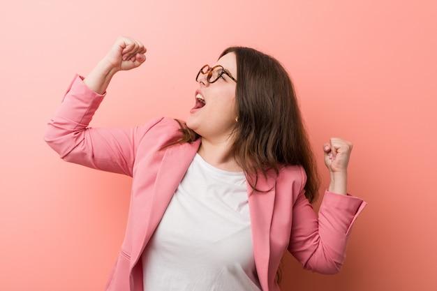 Giovani più la donna caucasica di affari di dimensione che alza il pugno dopo una vittoria, concetto del vincitore.