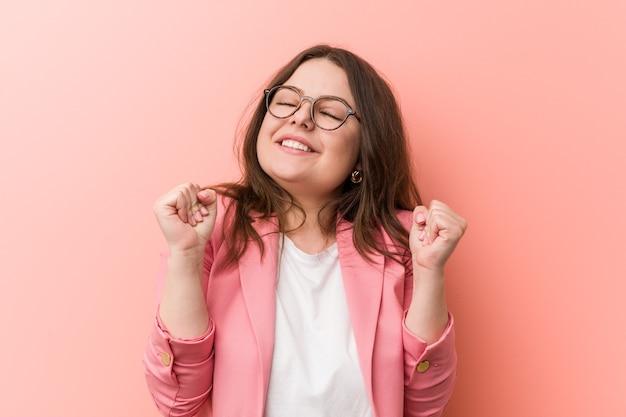 Giovane donna caucasica di affari di dimensioni più grandi che alza il pugno, sentendosi felice e di successo. concetto di vittoria.