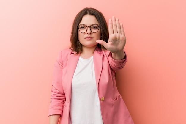 Young plus size donna d'affari caucasici in piedi con la mano tesa mostrando il segnale di stop, impedendoti.