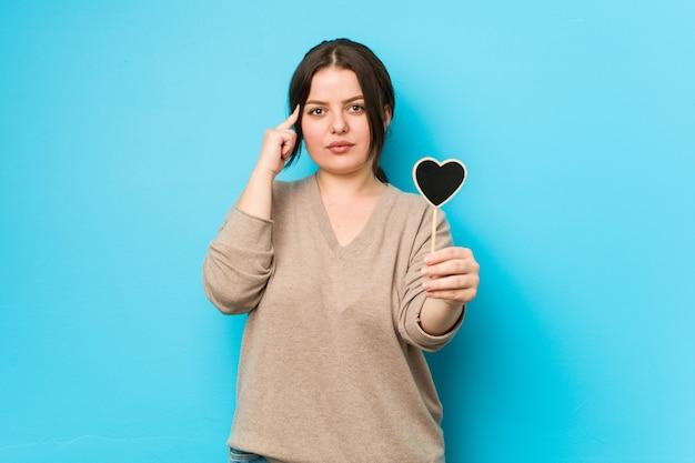 Giovane donna formosa plus size che tiene una forma di cuore che punta la tempia con il dito, pensando, concentrata su un compito.