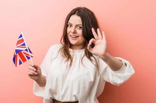 Giovane donna curvy plus size che tiene una bandiera del regno unito allegro e fiducioso che mostra gesto giusto.