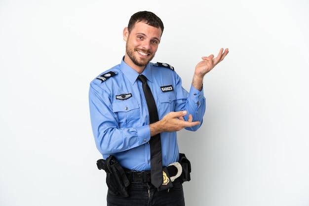 Giovane uomo brasiliano della polizia isolato su sfondo bianco che allunga le mani di lato per invitare a venire