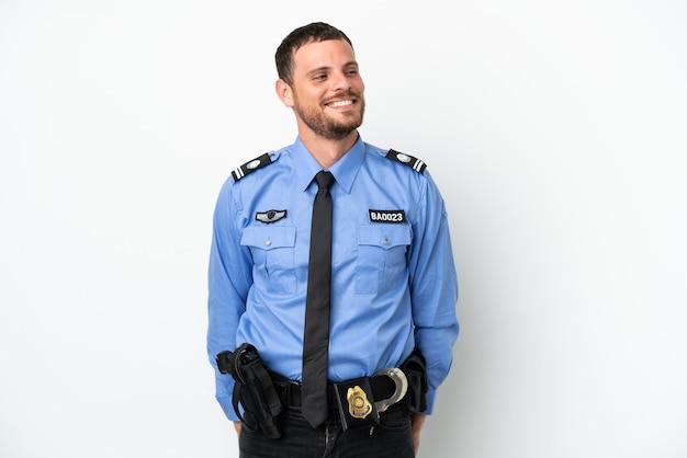 Giovane uomo brasiliano della polizia isolato su sfondo bianco guardando di lato e sorridente