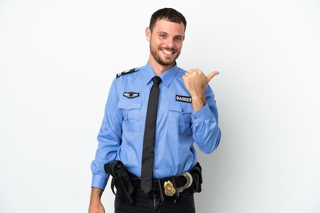 Giovane uomo brasiliano della polizia isolato su sfondo bianco rivolto verso il lato per presentare un prodotto