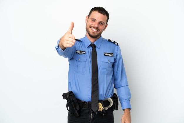 Giovane uomo brasiliano della polizia isolato su sfondo bianco che stringe la mano per aver chiuso un buon affare