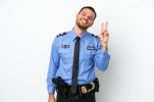 Giovane uomo brasiliano della polizia isolato su fondo bianco che sorride e che mostra il segno di vittoria