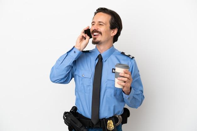 Giovane poliziotto su sfondo bianco isolato che tiene caffè da portare via e un cellulare