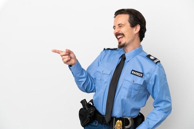 Giovane poliziotto su sfondo bianco isolato che punta il dito a lato e presenta un prodotto