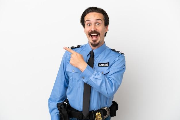 Giovane poliziotto su sfondo bianco isolato sorpreso e indicando il lato