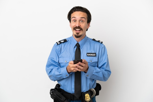 Giovane poliziotto su sfondo bianco isolato sorpreso e inviando un messaggio