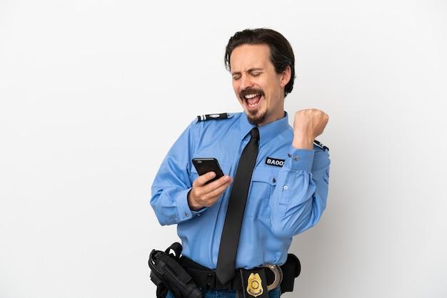 Giovane poliziotto su sfondo bianco isolato con telefono in posizione di vittoria