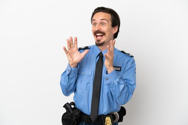 Giovane poliziotto su sfondo bianco isolato con espressione facciale a sorpresa